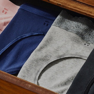 Drawer with folded underwear in multiple colors.