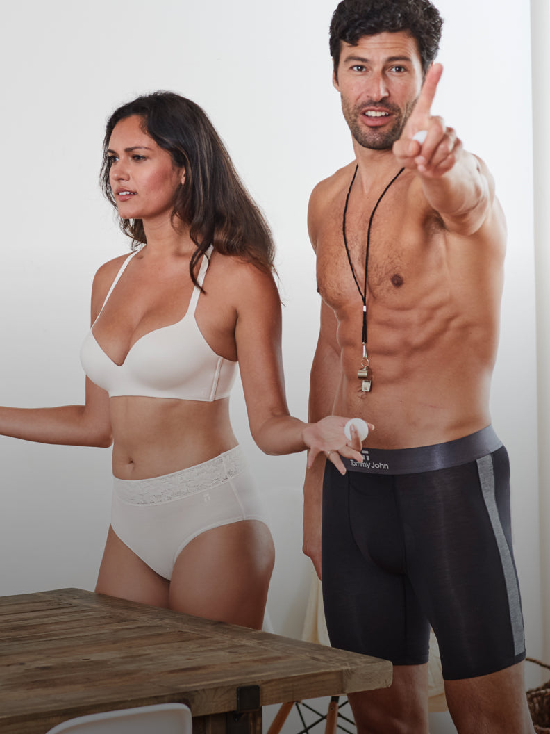 Male model standing in black boxer brief underwear with female model in soft pink bra and high rise brief underwear.